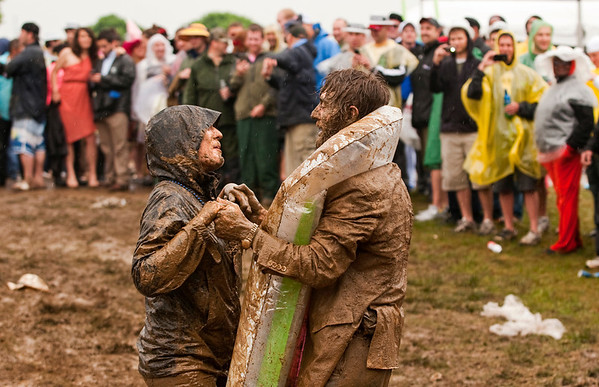 Vinnie Morrissey, of Omaha, Neb., helps Linea Webb, of Louisville, stand up after they both slid down a muddy embankment in the Infield at Churchill Downs during the 139th Kentucky Derby in Louisville on Saturday afternoon. Staff photo by Christopher Fryer