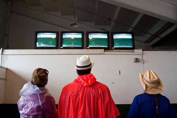 From left, Elizabeth and Kevin Knuckley, of Fort Worth, Texas, stand next to Evelyn Stark, of Las Vegas, while they watch the third race of the day on monitors next to wagering windows at the 139th Kentucky Derby at Churchill Downs in Louisville on Saturday. Staff photo by Christopher Fryer