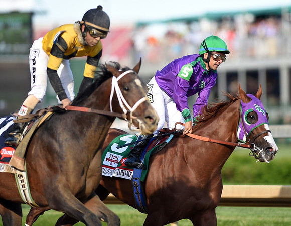 Right to Left: Jockey Victor Espinoza, riding California Chrome passes Commanding Curve on the inside of the track after completing the 140th Kentucky Derby at Churchill Downs on Saturday. California Chrome took the victory, with Commanding Curve in second.<br /> Staff photo by Tyler Stewart