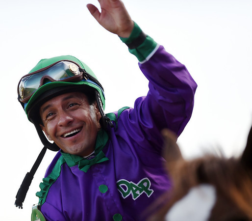 California Chrome jockey, Victor Espinoza, smiles and waves to the crowd after winning the 140th Kentucky Derby at Churchill Downs on Saturday.<br /> Staff photo by Tyler Stewart