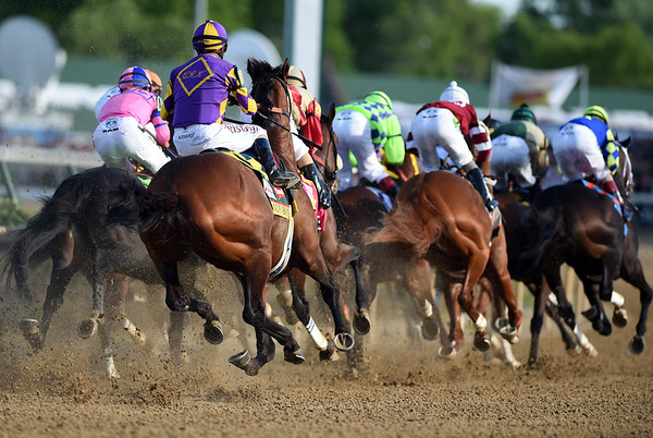 Jockeys and horses barrel through the first turn of the 140th Kentucky Derby at Churchill Downs on Saturday. <br /> Staff photo by Tyler Stewart