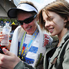 Winner of the women's marathon, Erin Goff of Denver, Colo., and formerly of Joplin, watches a video of herself crossing the finish line recorded by her 12-year-old daughter Parker Goff-Chrisbens (right) Sunday morning, Oct. 13, 2013, at the finish line for the Mother Road Marathon at the Joplin Athletic Complex.<br /> Globe | T. Rob Brown