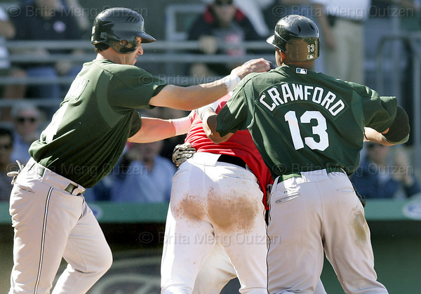 Tampa Bay Devil Rays Carl Crawford, right, and teammate Greg Norton, left, take down Boston Red Sox pitcher Julian Tavarez, center, after Tavarez fought Tampa Bay Devil Rays base runner Joey Gathright following an incident while trying to score in the eighth inning of their spring training baseball game in Fort Myers, Fla., Monday March 27, 2006.  Both benches cleared after the incident. (AP Photo/Brita Meng Outzen)
