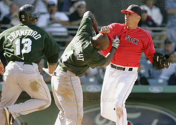 Boston Red Sox pitcher Julian Tavarez, right, lands a punch during a fight with Tampa Bay Devil Rays base runner Joey Gathright after he slid into Tavarez while trying to score on a hit by Julio Lugo in the eighth inning of their spring training baseball game in Fort Myers, Fla., Monday March 27, 2006.  Both benches cleared after the incident.  At left running to Gathright's aid is teammate Carl Crawford.  (AP Photo/Brita Meng Outzen)
