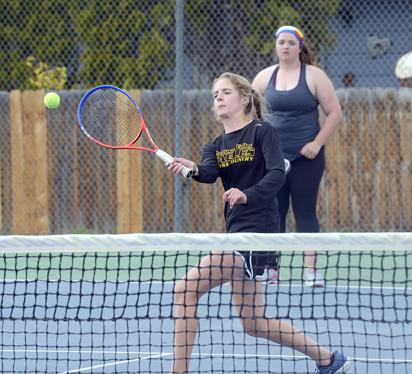 . Emily Black of Thompson Valley concentrates on her return as her partner on the No. 2 doubles team, Kaitlyn Morris, looks on during Thursday\'s home match with Mountain View. (Mike Brohard/Loveland Reporter-Herald)
