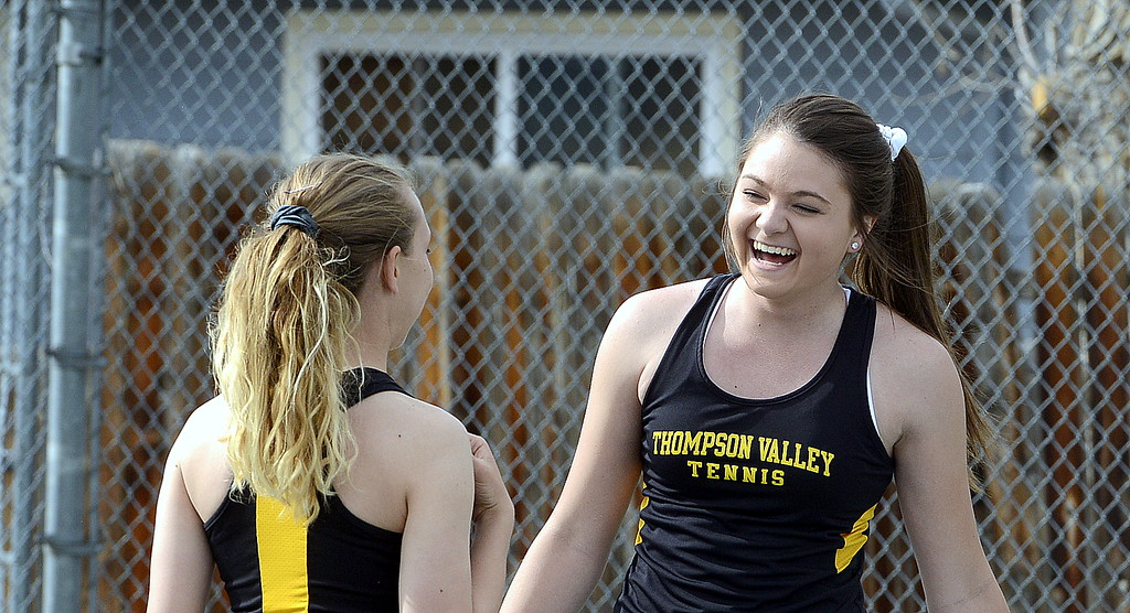 . Thompson Valley\'s No. 3 doubles team of Lacy Sauer (left) and Kaelyn Giefer share a laugh during a break in their match with Mountain View on Thursday. (Mike Brohard/Loveland Reporter-Herald)