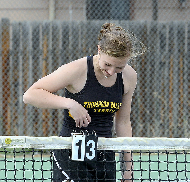 . Thompson Valley\'s Autumn Porter gleefully turns the score card as she and No. 4 doubles partner Sydney Laws take a lead on Mountain View in the second set of their match with Mountain View on Thursday. (Mike Brohard/Loveland Reporter-Herald)