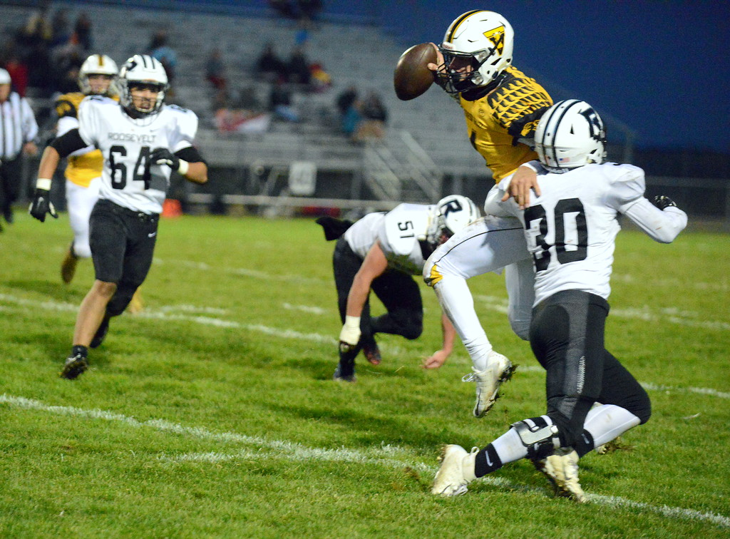 . Thompson Valley quarterback Cam Nellor jumps to his right to try to avoid the tackle of Roosevelt\'s Conner Doucette during Thursday\'s game  at Patterson Stadium. (Mike Brohard/Loveland Reporter-Herald)