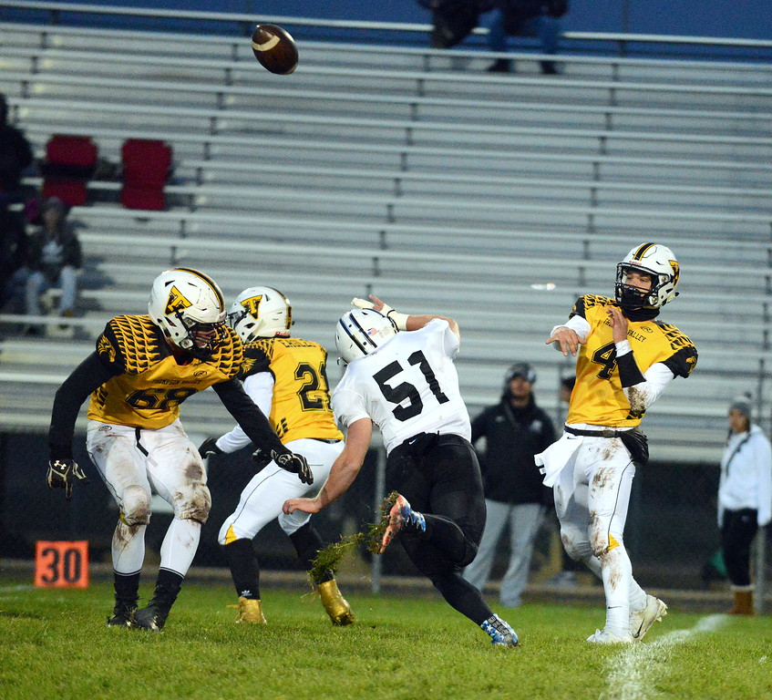 . Thompson Valley quarterback Cam Nellor releases his pass as Roosevelt\'s Garrett Padgett rushes during Thursday\'s game  at Patterson Stadium. (Mike Brohard/Loveland Reporter-Herald)