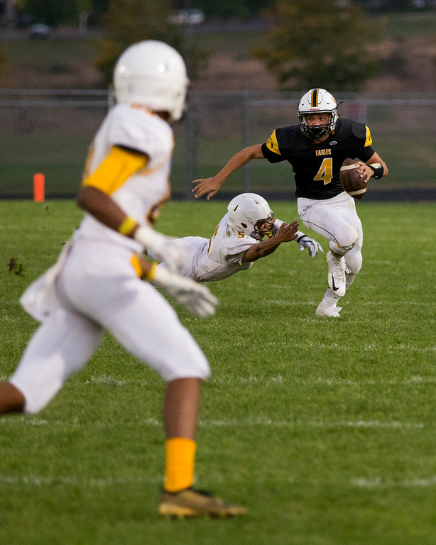 . Thompson Valley quarterback Cam Nellor (4) scrambles away from a sack against Thomas Jefferson Thursday evening Sept., 27, 2018 at Patterson Field in Loveland. (Michael Brian/For the Reporter-Herald)