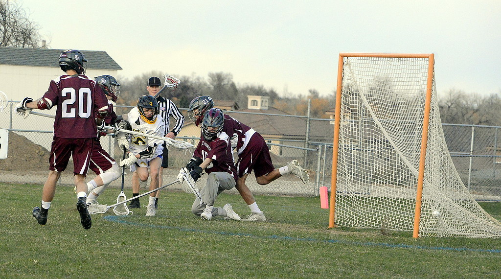 . Thompson Valley\'s Greg Bilek weaves through a crowd of Cheyenne Mountain defenders to beat goalie Liam Hybl with a low shot in Monday\'s game at Patterson Stadium. The Eagles won 13-12. (Mike Brohard/Loveland Reporter-Herald).