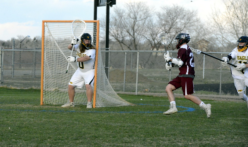 . Thompson Valley goalie Corbin Shilling defends the post as Cheyenne Mountain\'s Eli Loomis closes in during Monday\'s game at Patterson Stadium. The Eagles posted a 13-12 win. (Mike Brohard/Loveland Reporter-Herald).