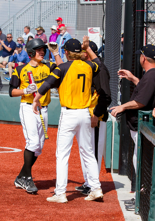 . Thompson Valley\'s Cameron Nallor (4), left, is welcomed back to the dugout by teammate Tommy Crews (7), center, after scoring a run against Evergreen Friday morning May 26, 2017 at Metro State\'s Regency Athletic Complex during the 2017 CHSAA Baseball State Championships Final Four in Denver. The Eagles won the game 12-9 to advance to Saturday play. (Michael Brian/For the Reporter-Herald)