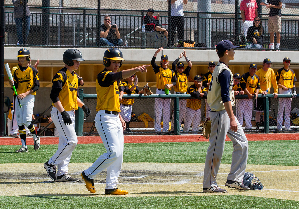 . Thompson Valley\'s Matt Berg (2), center, points to teammate Adrian Juarez (10) on first base after Juarez\'s hit scored two runs against Evergreen Friday morning May 26, 2017 at Metro State\'s Regency Athletic Complex during the 2017 CHSAA Baseball State Championships Final Four in Denver.  The Eagles beat the Cougars, 12-9. (Michael Brian/For the Reporter-Herald)