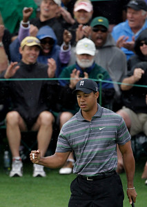 Spectators reacts as Tiger Woods pumps his fist after his birdie putt on the ninth green during the first round of the Masters golf tournament in Augusta, Ga., Thursday, April 8, 2010. (AP Photo/Morry Gash)