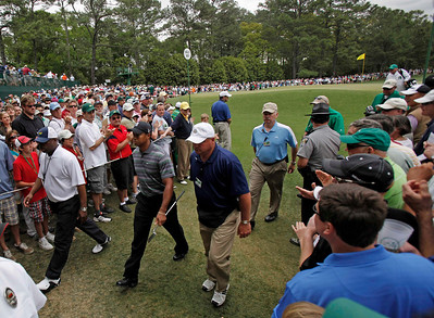 Escorted by security personnel, Tiger Woods walks to the second tee during the first round of the Masters golf tournament in Augusta, Ga., Thursday, April 8, 2010. (AP Photo/Rob Carr)