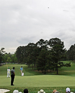 Tiger Woods waits to putt on the third green as a plane tows a banner over the Augusta National Golf Club during the first round of the Masters golf tournament in Augusta, Ga., Thursday, April 8, 2010. (AP Photo/Rob Carr)