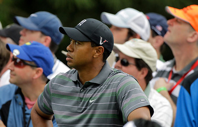 Tiger Woods watches K.J. Choi of South Korea's drive off the sixth tee during the first round of the Masters golf tournament in Augusta, Ga., Thursday, April 8, 2010. (AP Photo/Charlie Riedel)