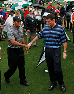Tiger Woods, left, is congratulated by his agent Mark Steinberg after his first round of the Masters golf tournament in Augusta, Ga., Thursday, April 8, 2010. (AP Photo/Rob Carr)