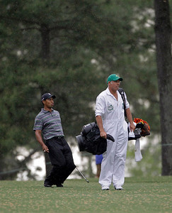 Caddie Steve Williams keeps an eye out as Tiger Woods reacts to his approach shot on the ninth fairway during the first round of the Masters golf tournament in Augusta, Ga., Thursday, April 8, 2010. (AP Photo/Morry Gash)