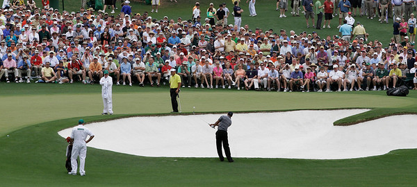 K.J. Choi of South Korea, top left, watches as Tiger Woods chips to the second green during the first round of the Masters golf tournament in Augusta, Ga., Thursday, April 8, 2010. (AP Photo/Rob Carr)