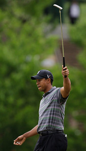 Tiger Woods raises putter after a birdie putt on the 15th green during the first round of the Masters golf tournament in Augusta, Ga., Thursday, April 8, 2010. (AP Photo/Charlie Riedel)