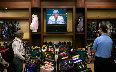 """Shopper Esat Yurekli, of Turkey, left, and sales associate Ian McGowan watch the Tiger Woods news conference at New York Golf Center in New York, Monday, April 5, 2010.  While acknowledging he made some """"incredibly poor decisions"""" in his personal life, Tiger Woods still thinks he can win the Masters, even coming back from a five-month layoff. (AP Photo/David Goldman)"""
