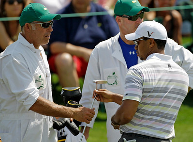 Tiger Woods, right, hands his putter to caddie Steve Williams on the 18th green after his practice round for the Masters golf tournament in Augusta, Ga., Monday, April 5, 2010. The tournament begins Thursday, April, 8. (AP Photo/Chris O'Meara)