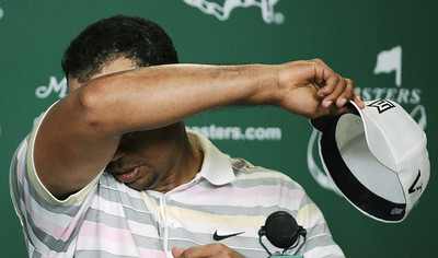 Tiger Woods wipes his forehead before his press conference at the Masters golf tournament in Augusta, Ga., Monday, April 5, 2010. The tournament begins Thursday, April, 8. (AP Photo/Harry How, Pool)
