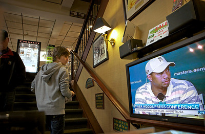 """Pierre Simon, 16, of Dunkirk, France, watches the Tiger Woods news conference while shopping at New York Golf Center in New York, Monday, April 5, 2010. While acknowledging he made some """"incredibly poor decisions"""" in his personal life, Tiger Woods still thinks he can win the Masters _ even coming back from a five-month layoff. (AP Photo/David Goldman)"""