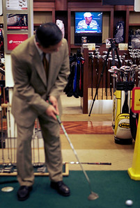 "The Tiger Woods news conference is broadcast in the background as a shopper practices putting at New York Golf Center in New York, Monday, April 5, 2010. While acknowledging he made some ""incredibly poor decisions"" in his personal life, Woods still thinks he can win the Masters, even coming back from a five-month layoff. (AP Photo/David Goldman)"