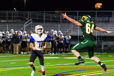 Quinn Gallagher (12) fires a pass over the outstretched arms of Andrew McIntosh (64).