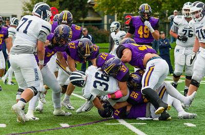 A host of Ephs defenders engulf Middlebury runningback Peter Scibilia.