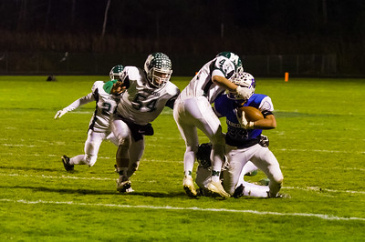 Gabe Davis (34) gets wrapped up for a loss by a host of Minnechaug defenders.