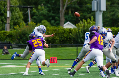 Luke Apuzzi (25) blasts Colby QB Jack O'Brien, forcing an errant throw.