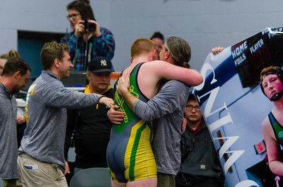 Shawn O'Shea Jr. gets hugs from his coaches as he celebrates his 100th win Saturday.