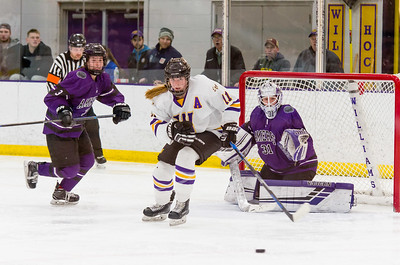 Abby Brustad (11) watches a shot carom off Amherst goaltender Caitlin Walker (31) late in the third period.
