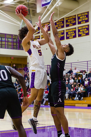 Brandon Arnold (5) goes for a high jump shot over Fru Che (25) during the first half.