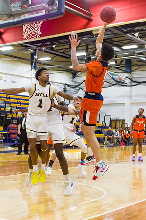 Salem State guard Chris MacDonald (2) goes up high to score over MCLA's Damon Daniel (1).