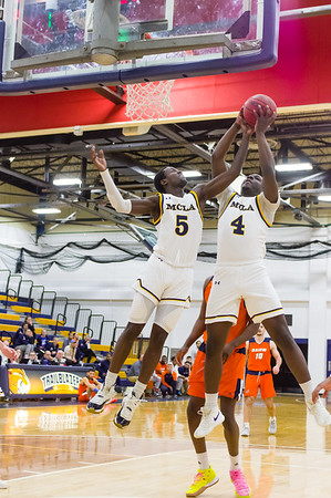 Bright Afful (4) pulls in a rebound in the first half, with a helping hand from Marius Turner (5).