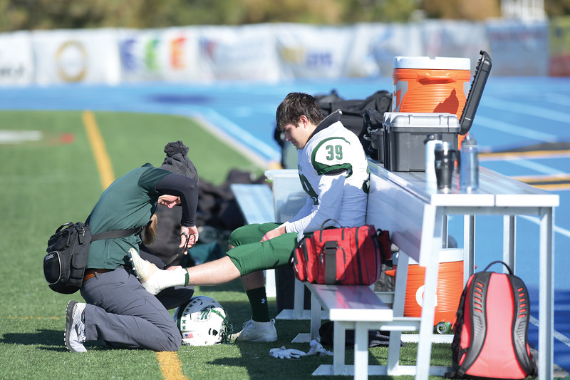 Matthew Gaston | The Sheridan Press<br>Tongue River's athletic trainer Jessica Garden works on full back Tony Perfetti's ankle at Homer Scott Field Saturday, Oct. 19, 2019.