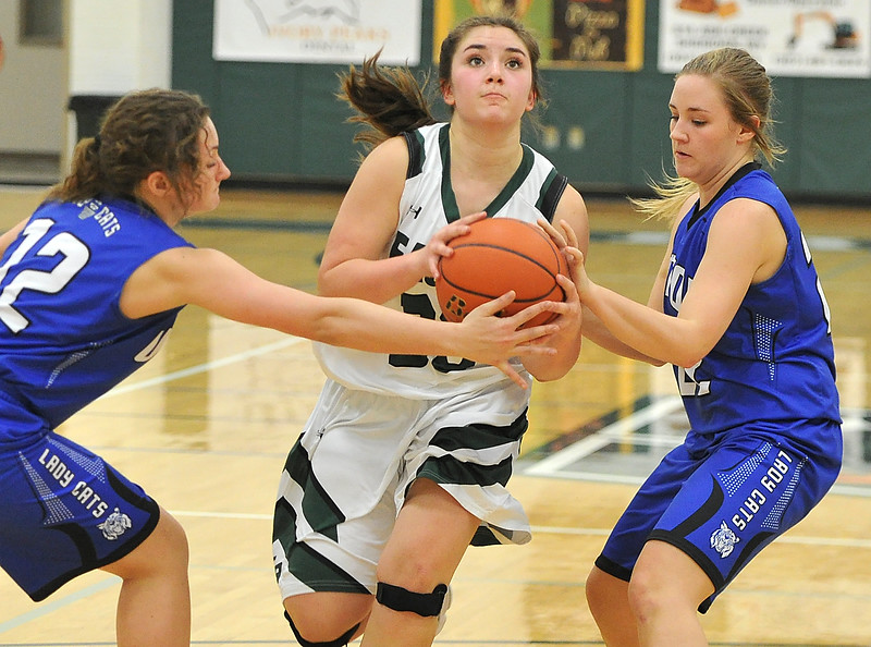 Justin Sheely | The Sheridan Press<br /> <br /> Tongue River's Zaveah Kobza, center, goes for a layup against Upton's Katlyn Louderback, left, and Lainee Claycomb at Tongue River High School Friday, Feb. 2, 2018. The Lady Eagles won 59-24.