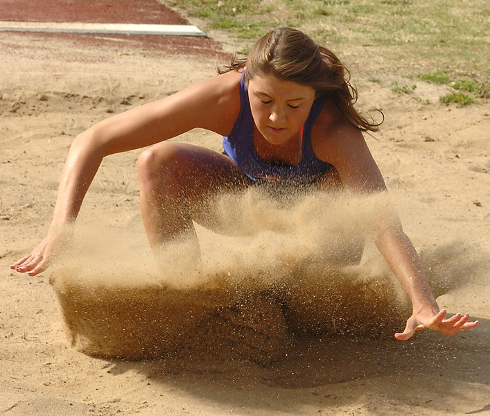 Volunteer's Emily Armstrong lands in the pit during the girls long jump. Photo by Ned Jilton II
