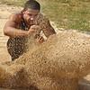 Dobyns Bennett's DJ Jones kicks up a cloud of sand as he lands in the long jump pit. Photo by ned Jilton II