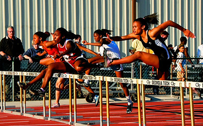 03-19-10  --ga tech track invite 01--  Lassiter's Gabrielle Piper, second from left, clears the first hurdle in the 100 hurdles on Friday evening at Georgia Tech.  STAFF/LAURA MOON.