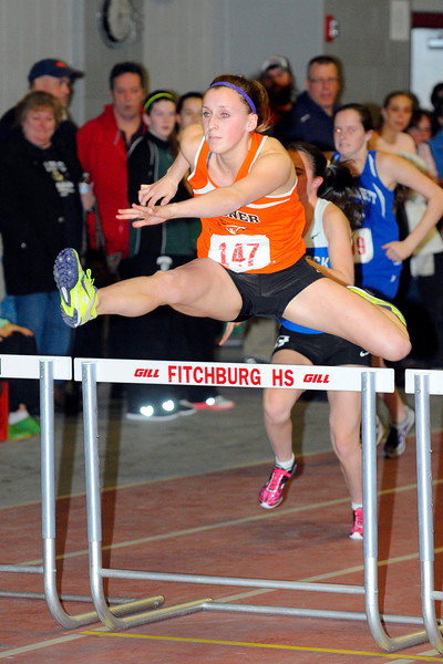 Gardner senior Aly Comeau, 18, races in the hurdles during Monday's Mid-Wach C league championships at Fitchburg High School, Monday night.<br /> SENTINEL & ENTERPRISE / BRETT CRAWFORD