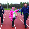 SENTINEL&ENTERPRISE/Ashley Green -- Sara Russo waves to the crowd as she helps Fitchburg State EMTs Pat McPherson (left) and Sam Carroll (right) carrying the Olympic torch during the opening ceremonies of the Special Olympics North Central School Day Games on Wednesday afternoon at Elliot Field in Fitchburg.