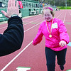 SENTINEL&ENTERPRISE/Ashley Green -- Nicole Caban, representing McKay Middle School, receives high fives as she approaches the finish line of the 200 meter race during the Special Olympics North Central School Day Games on Wednesday afternoon at Elliot Field in Fitchburg.