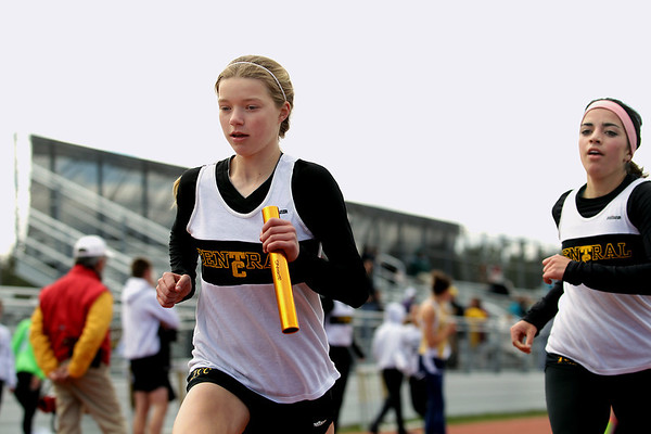 Record-Eagle/Keith King<br /> Traverse City Central's Graceanne Tarsa, left, runs after being handed the baton by teammate Kailey Mattarella, right, during the 3,200-meter relay Wednesday, April 11, 2012 at Traverse City Central High School.