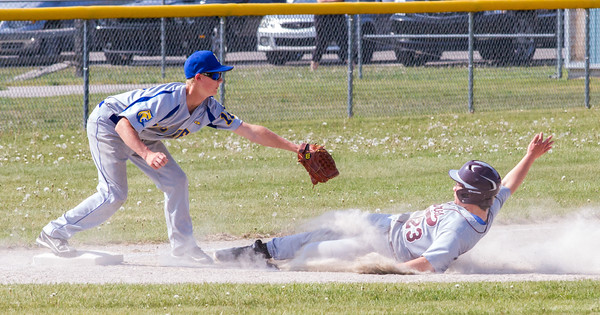 Record-Eagle/Brett A. Sommers  Traverse City Christian's Jake Bardenhagen (23) slides safely into third base under the tag of Buckley's Dawson Warren (10) during the opening baseball game of Monday's  doubleheader.